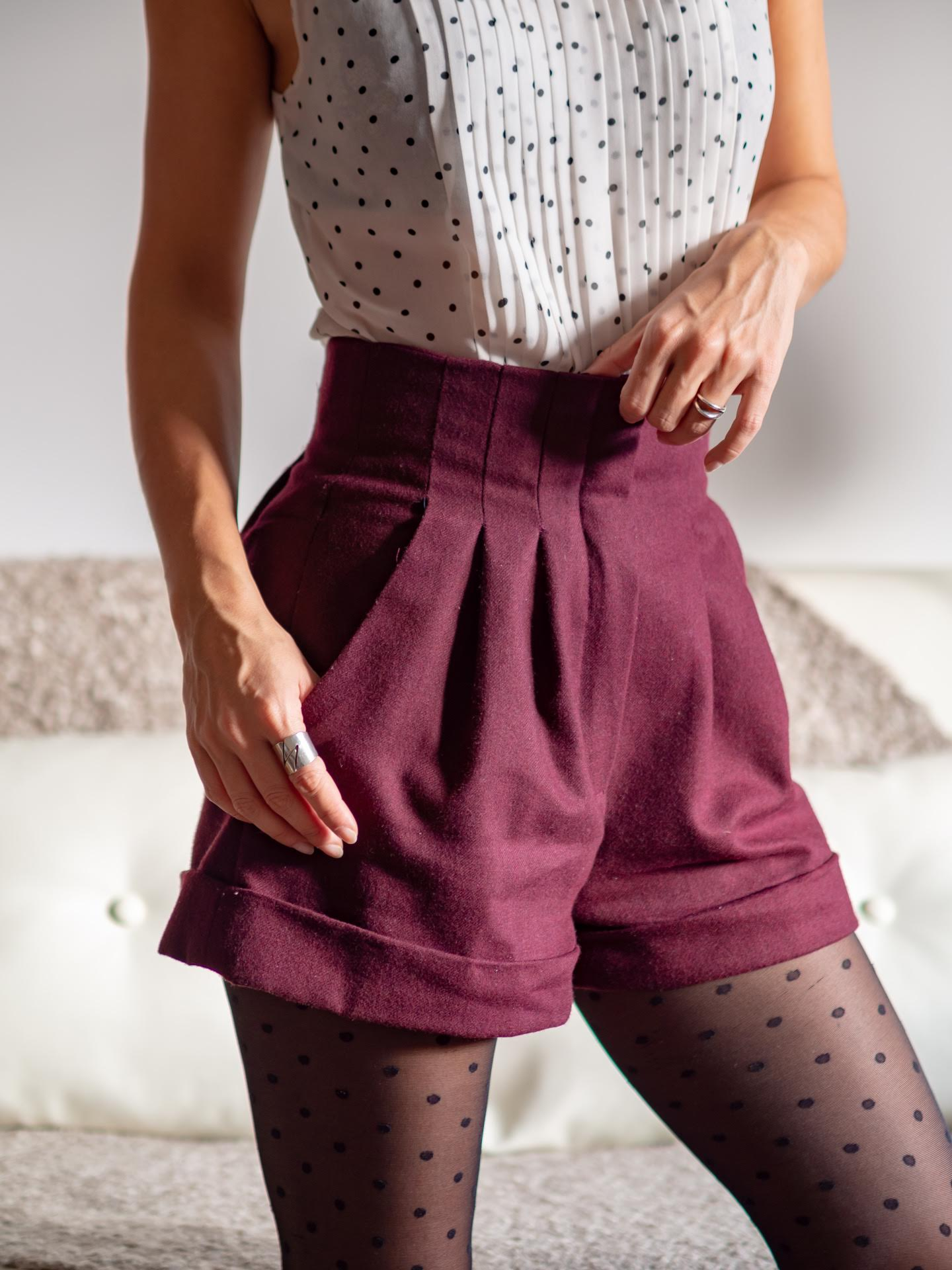 The image shows a close up of Giorgia wearing the shorts with a light blouse.