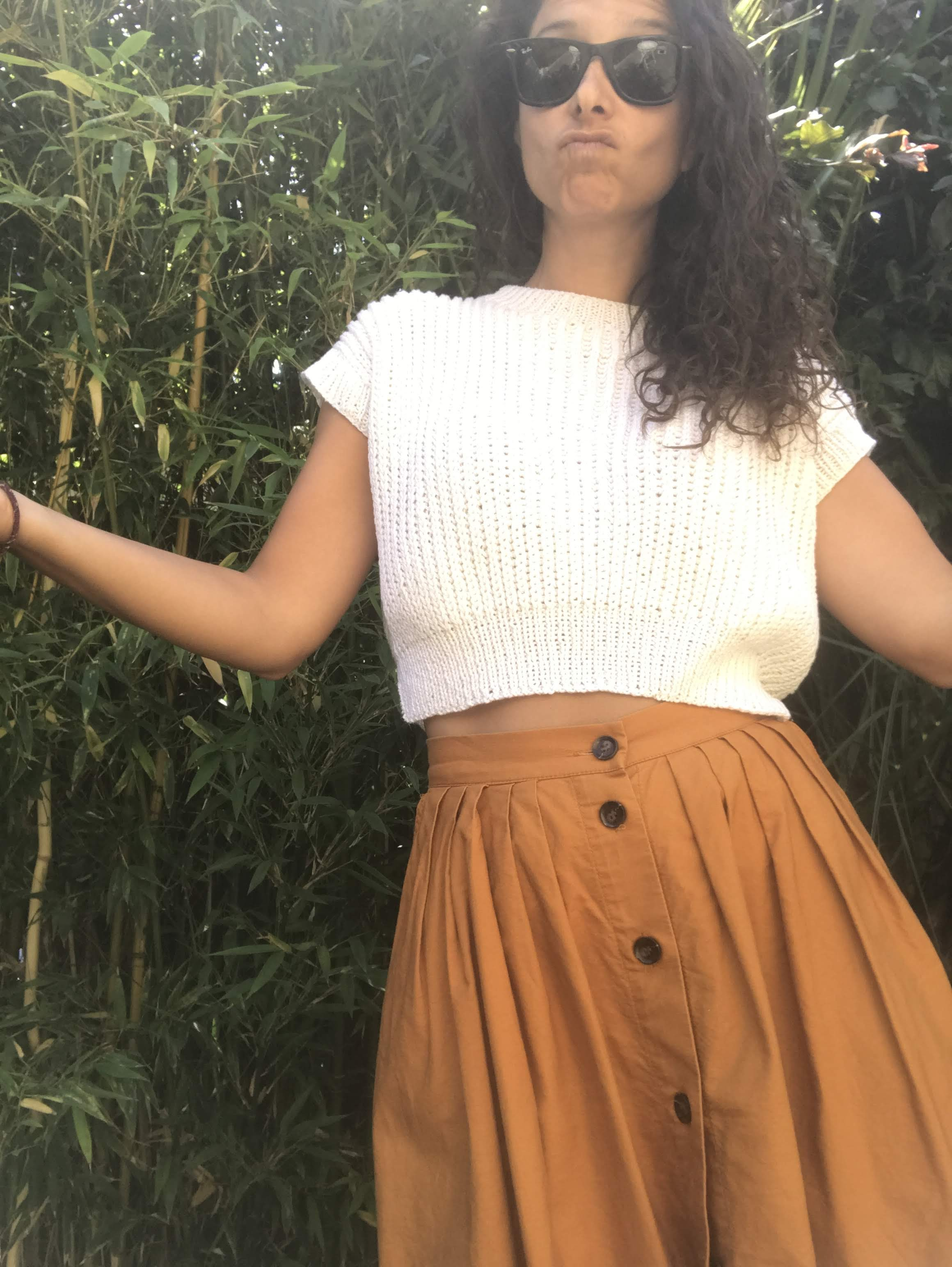 Giorgia is standing making a silly face and wearing the brand new jumper, paired with a pleated button down skirt.