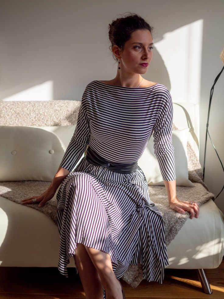 Giorgia sits on a sofa, looking away from the camera and towards the light. The picture shows a boat neckline dress, with 3/4 sleeves and a soft skirt that drapes gently on the sofa, showing a bit of ankle.